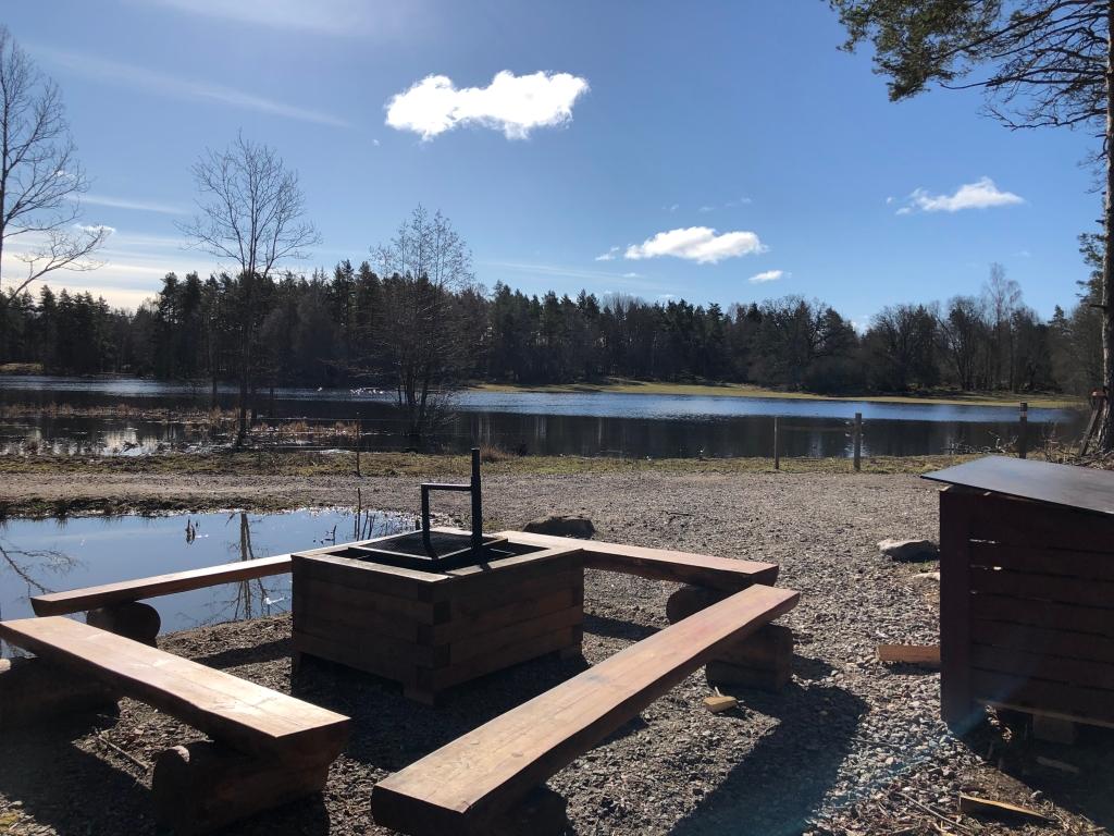 Rastplats vid Ullstämmaskogen med grillplats intill en liten sjö.