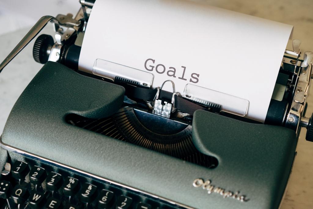 """Skrivmaskin med texten """"Goals"""" skrivet på ett papper."""