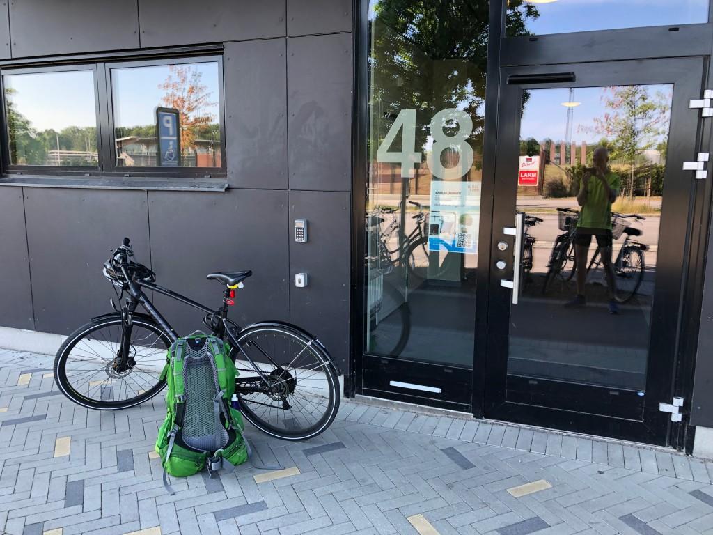Bild på min cykel och min ryggsäck utanför porten till min lägenhet