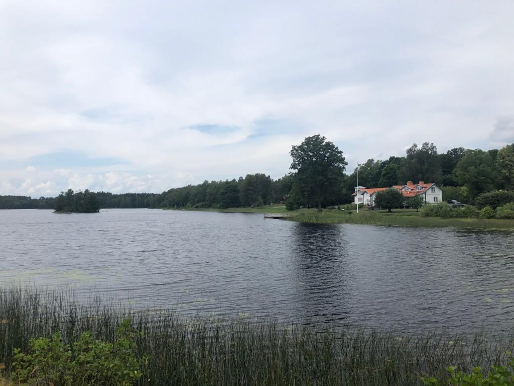 En herrgård vid en sjö och lätt molnigt på himlen.