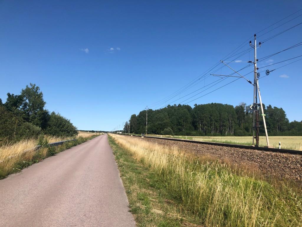 Liten bilväg jämte tågrälsen mellan Köping och Munktorp.