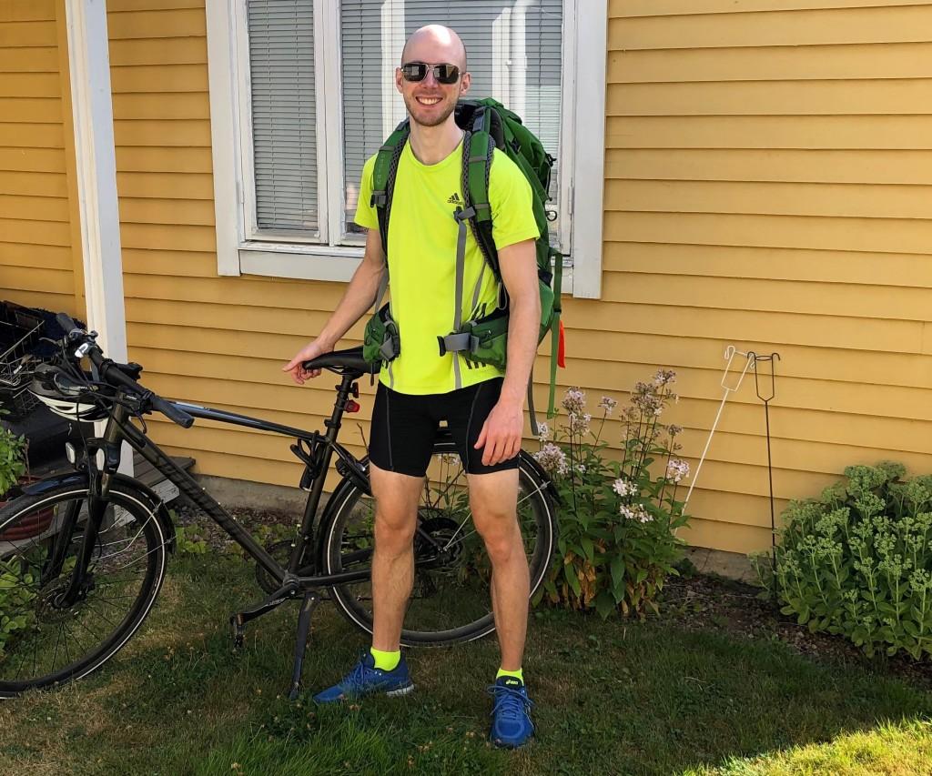 Jag med ryggsäck och solglasögon ståendes bredvid cykeln hemma i föräldrarnas trädgård.