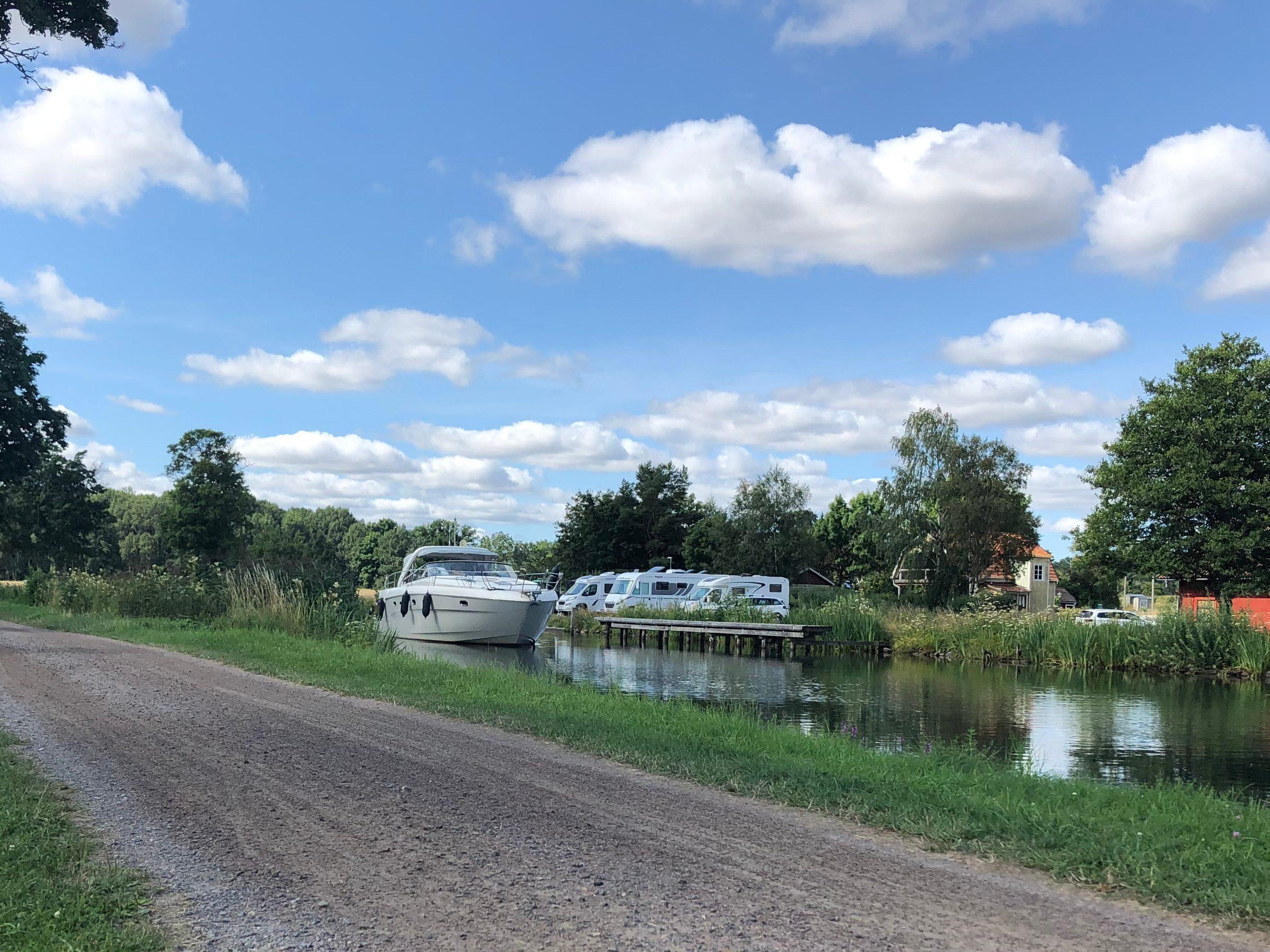 Göta kanal med en förbipasserande båt och cykelvägen bredvid