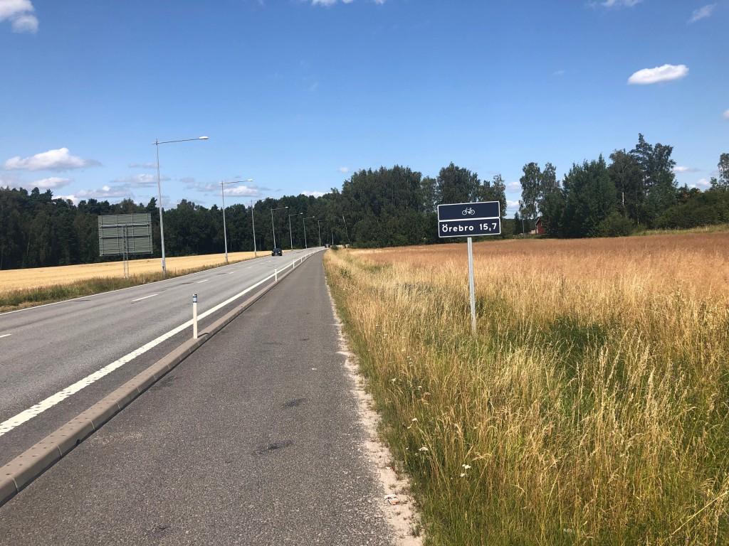 Skylt som visar 15,7 km till Örebro längs med Kumlavägen.